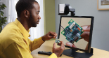 Photo: A man is using the SmartView 360 to work on a tiny object that looks like an electronic chip.