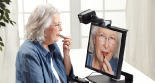 Photo: Elderly woman using the SmartView 360 with the camera facing her to help her apply makeup.